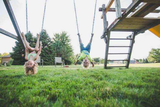 Jeunes enfants qui s'amusent en faisant de la balançoire dans le jardin