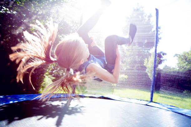 Petite fille qui fait un salto arrière dans un trampoline