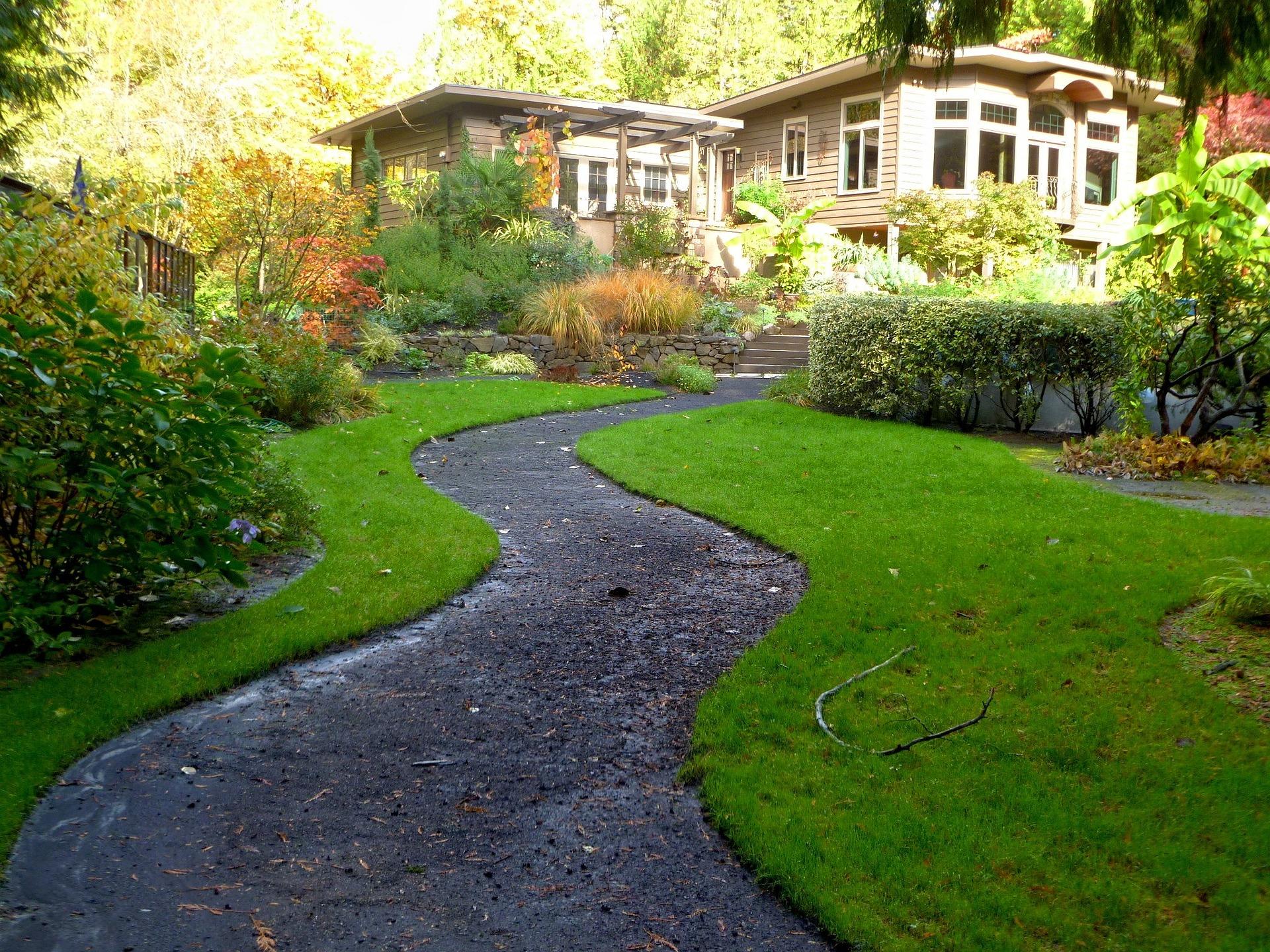 Maison avec grand jardin aménagé et bien entretenu parcouru par un petit chemin