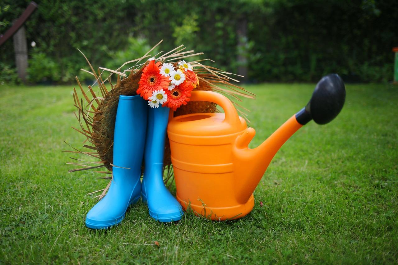 arrosoir en plastique orange, bottes en caoutchouc bleues et chapeau de paille avec des fleurs posés dans l'herbe
